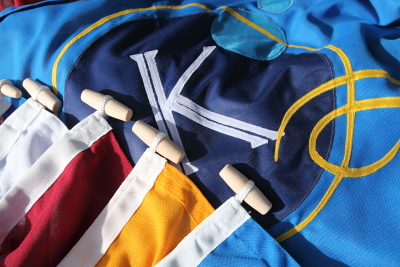Flags constructed from heavy duty polyester flag material using an applique method